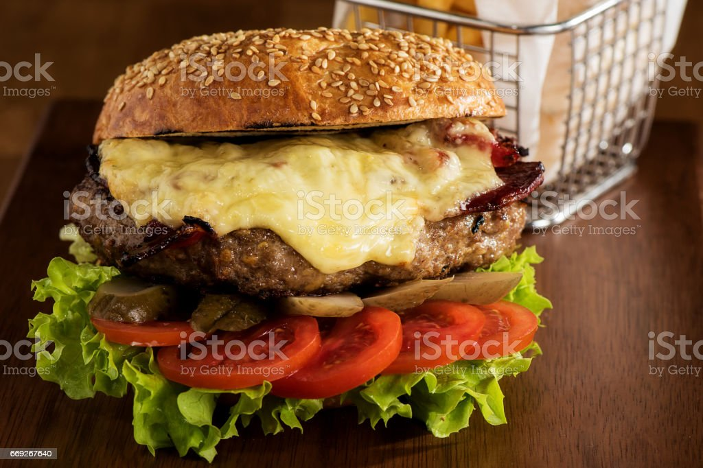 Cheeseburger and fried fries with wood background stock photo