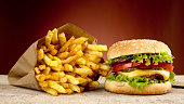 Cheeseburger, french fries on red background on wooden plank