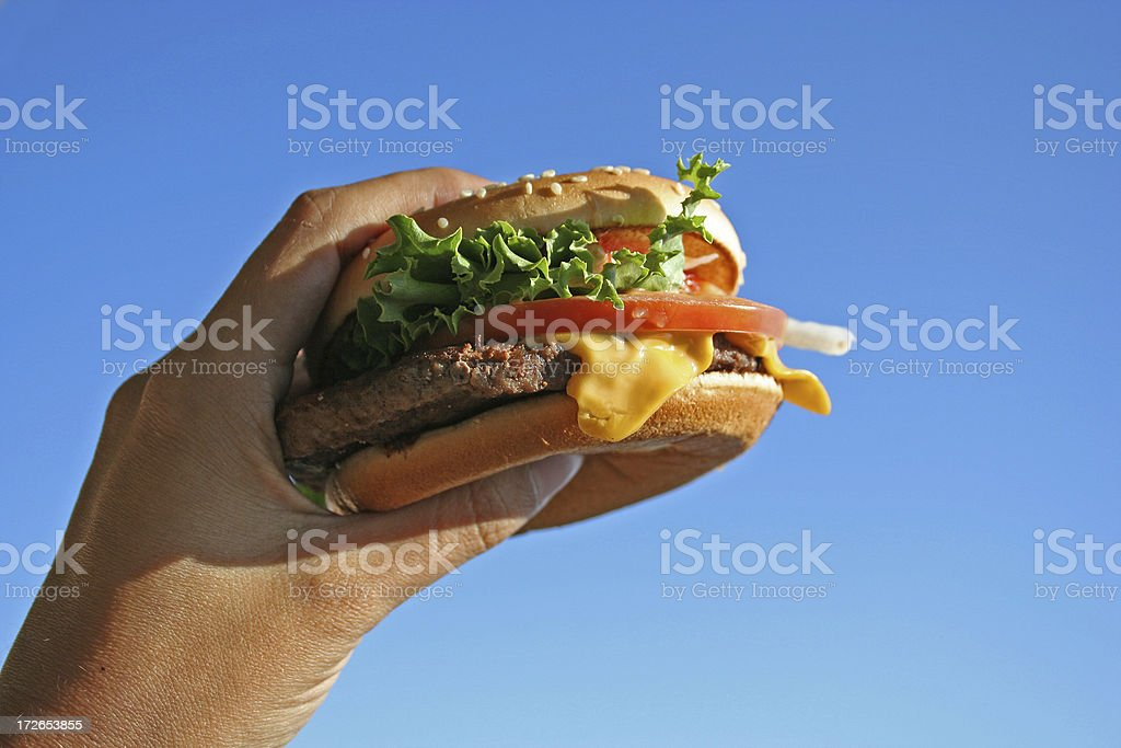 Cheeseburger in a left hand about to be eaten stock photo