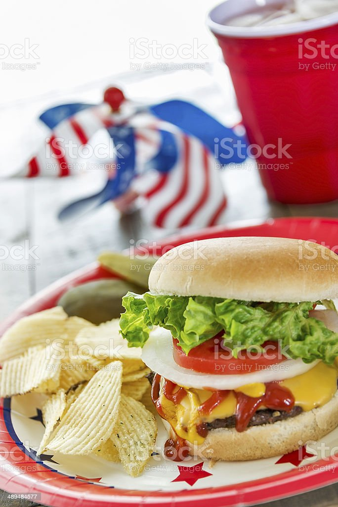 Cheeseburger loaded with toppings in a patriotic theme stock photo