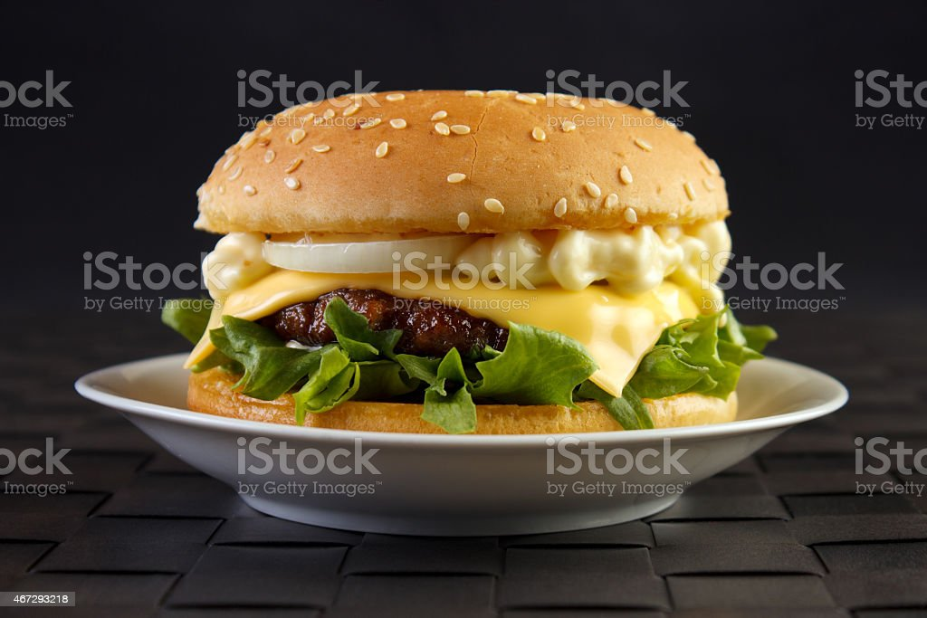 Cheeseburger on dish with black background royalty-free stock photo