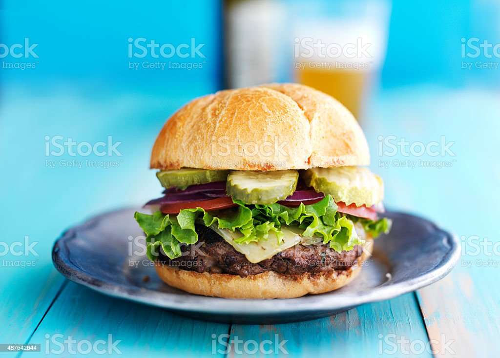 cheeseburger with beer in the background stock photo