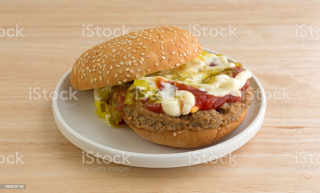 Cheeseburger with bun and condiments on small plate stock photo