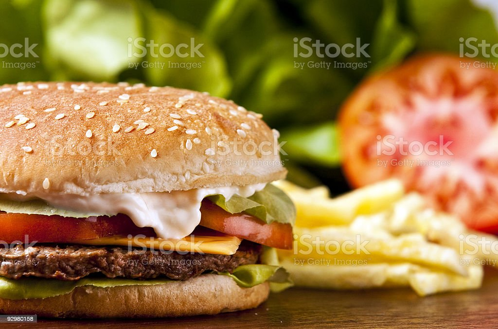 A cheeseburger with fries in the background stock photo