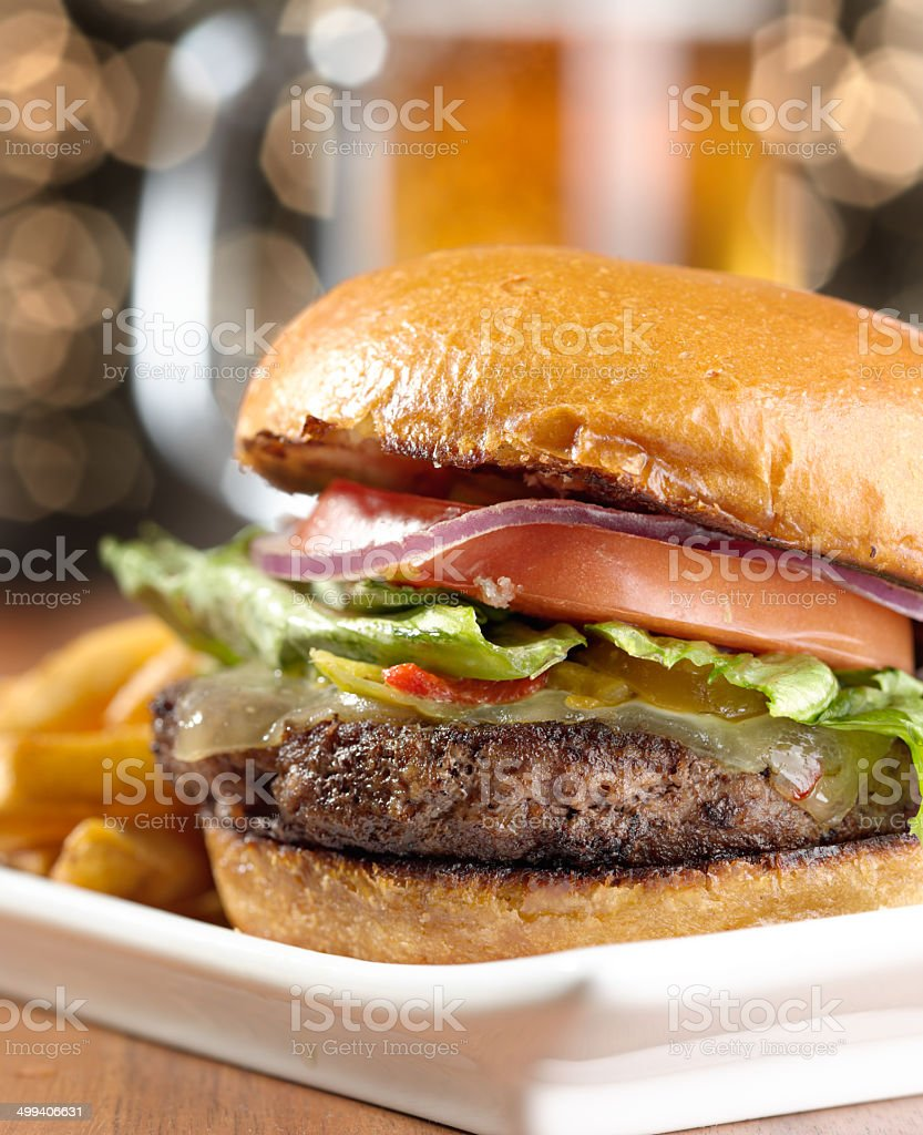 cheeseburger with mug of beer in background stock photo