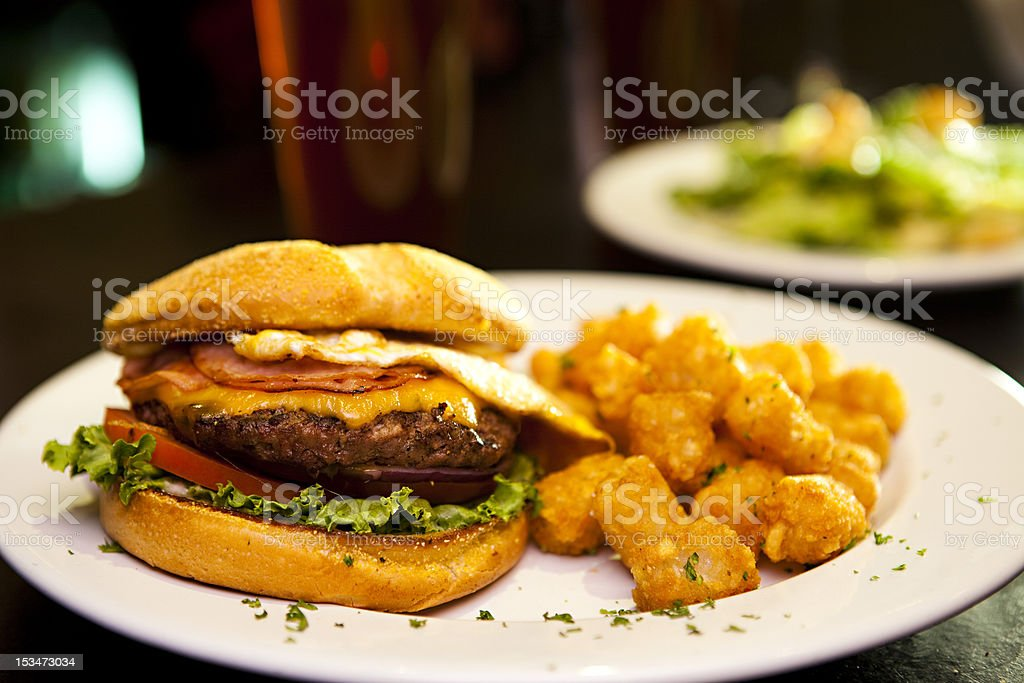Cheeseburger with tater tots and side salad stock photo