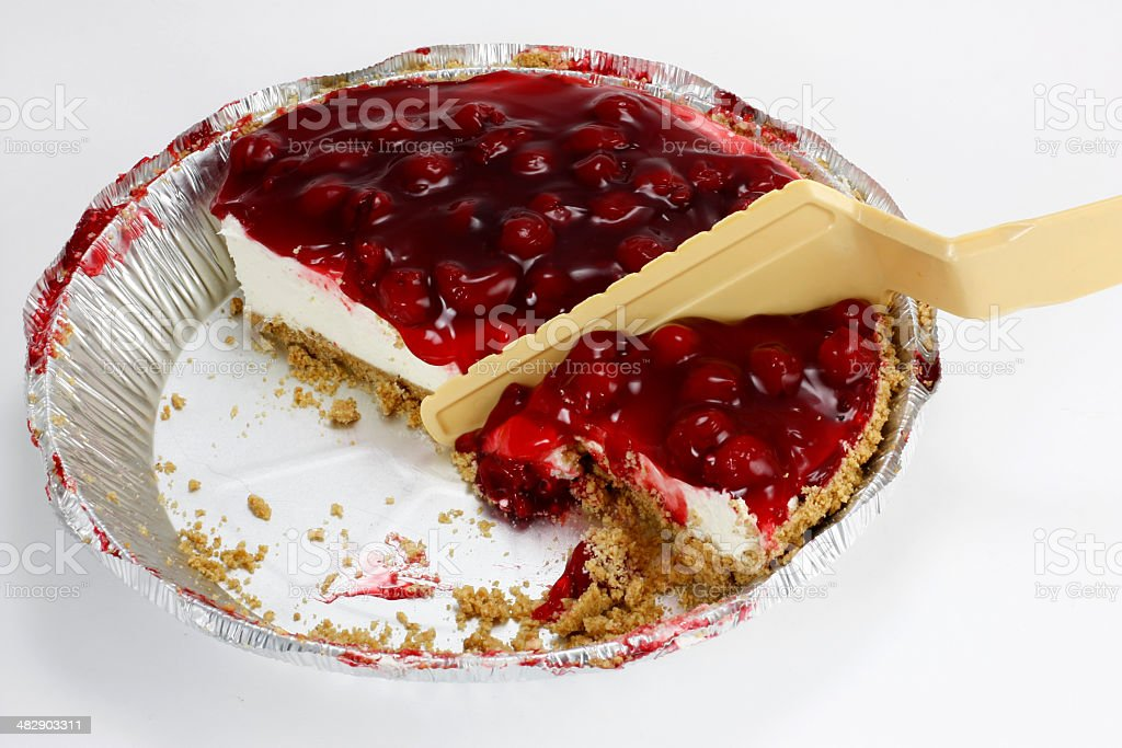 Cheesecake in pie pan with plastic server Focus stock photo