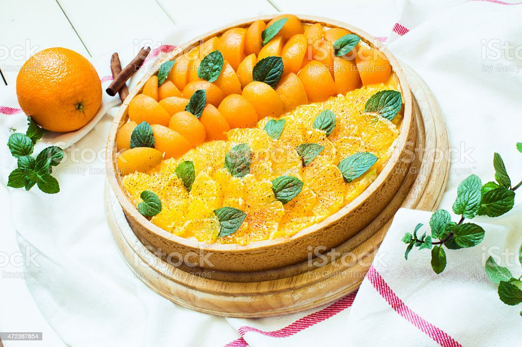 Cheesecake with peaches, oranges, cinnamon and mint stock photo