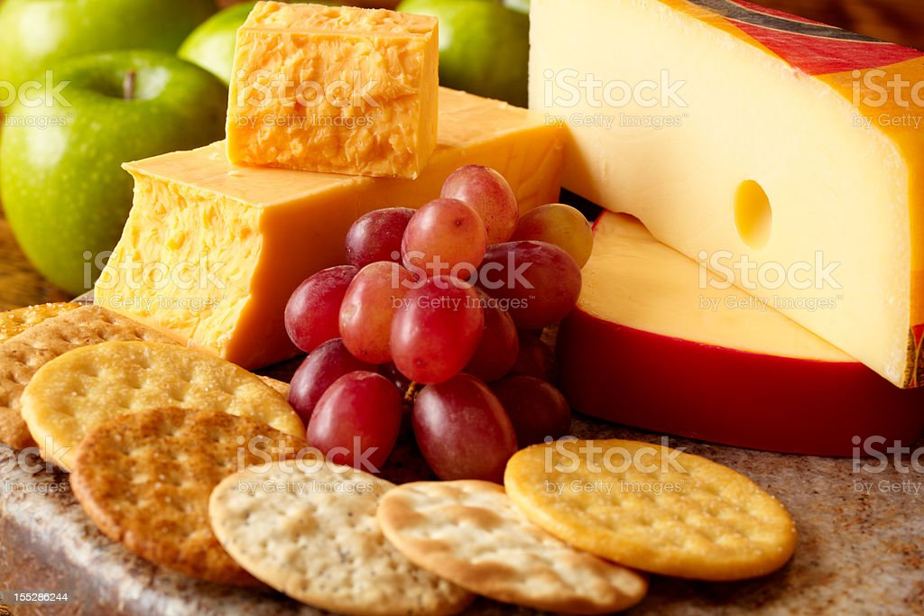 Cheeses and crackers with apples and grapes stock photo