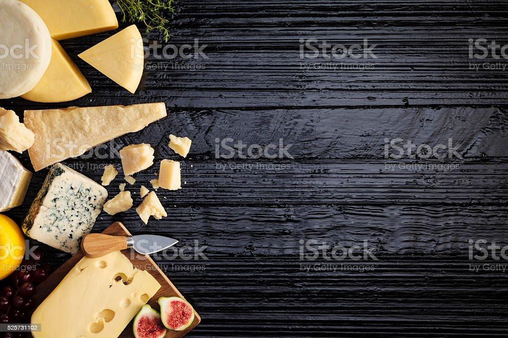 Cheeses on dark table stock photo