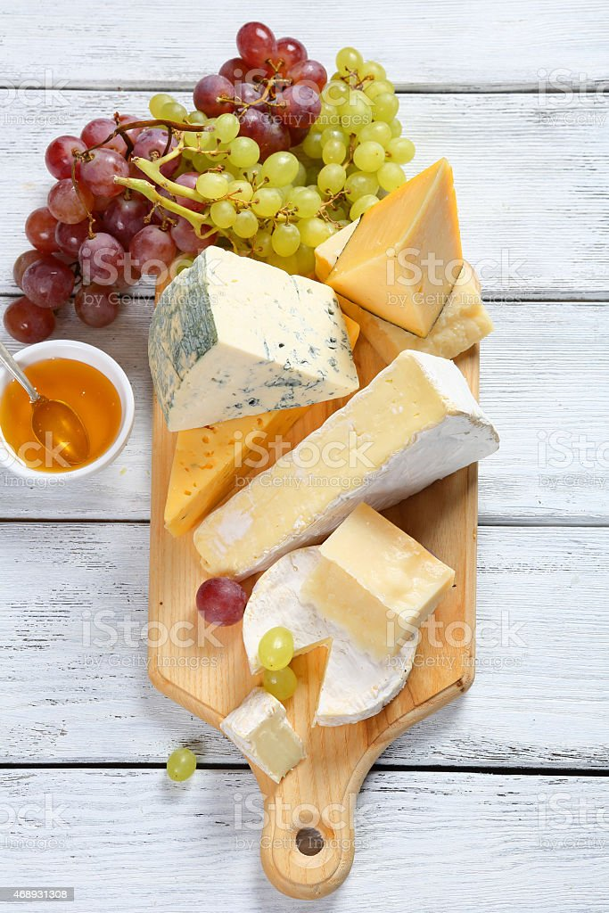 Cheeses with honey and grapes stock photo