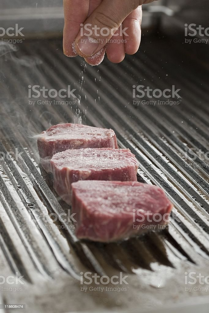 Chef add spycies to frying beef royalty-free stock photo