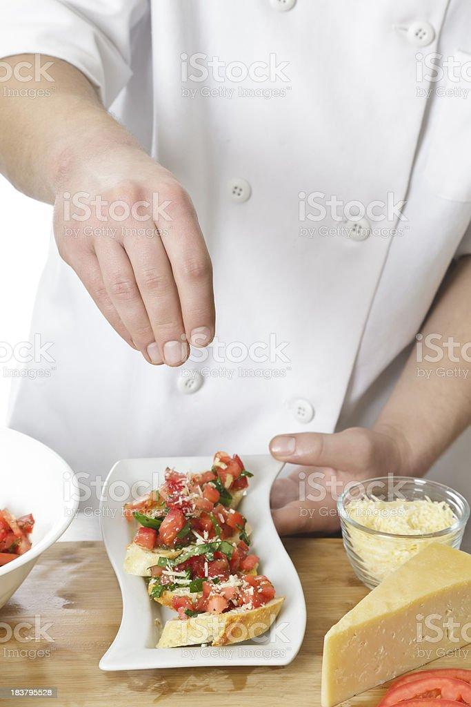Chef Adding Cheese to Plate of Bruschetta royalty-free stock photo
