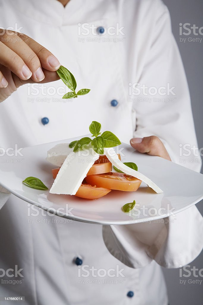 chef adding greens to dish royalty-free stock photo