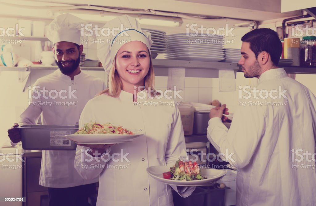 chef and his assistants preparing meal stock photo