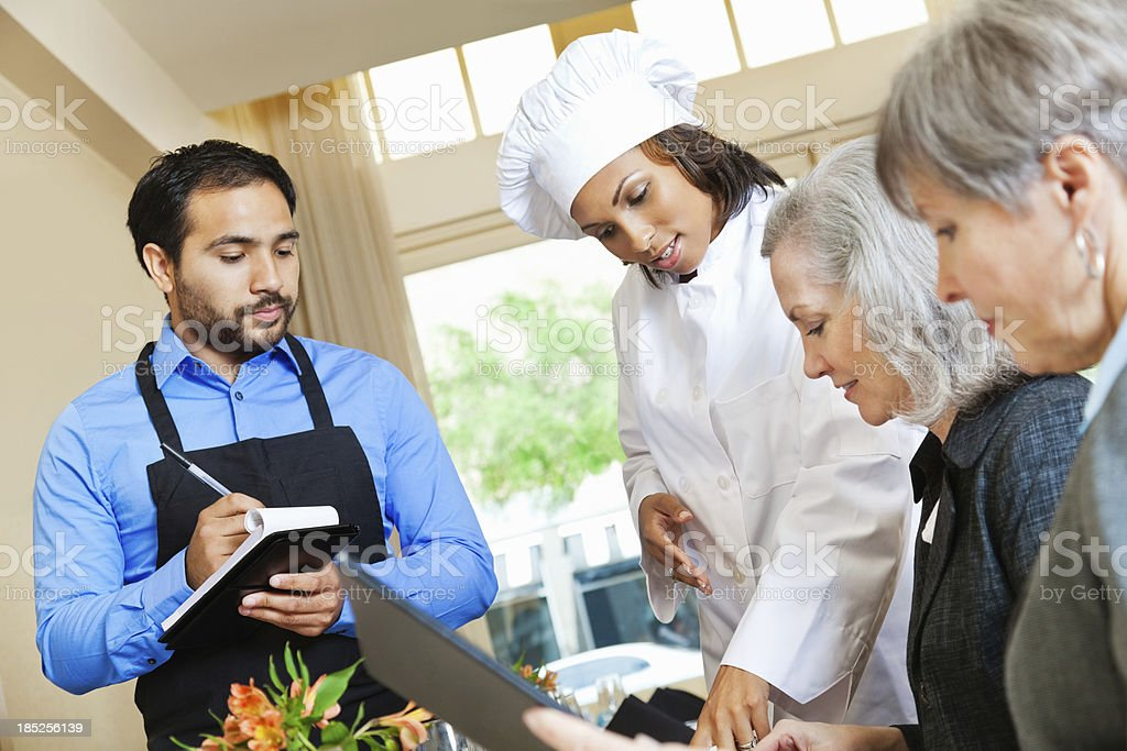 Chef and waiter helping customers in restaurant order royalty-free stock photo