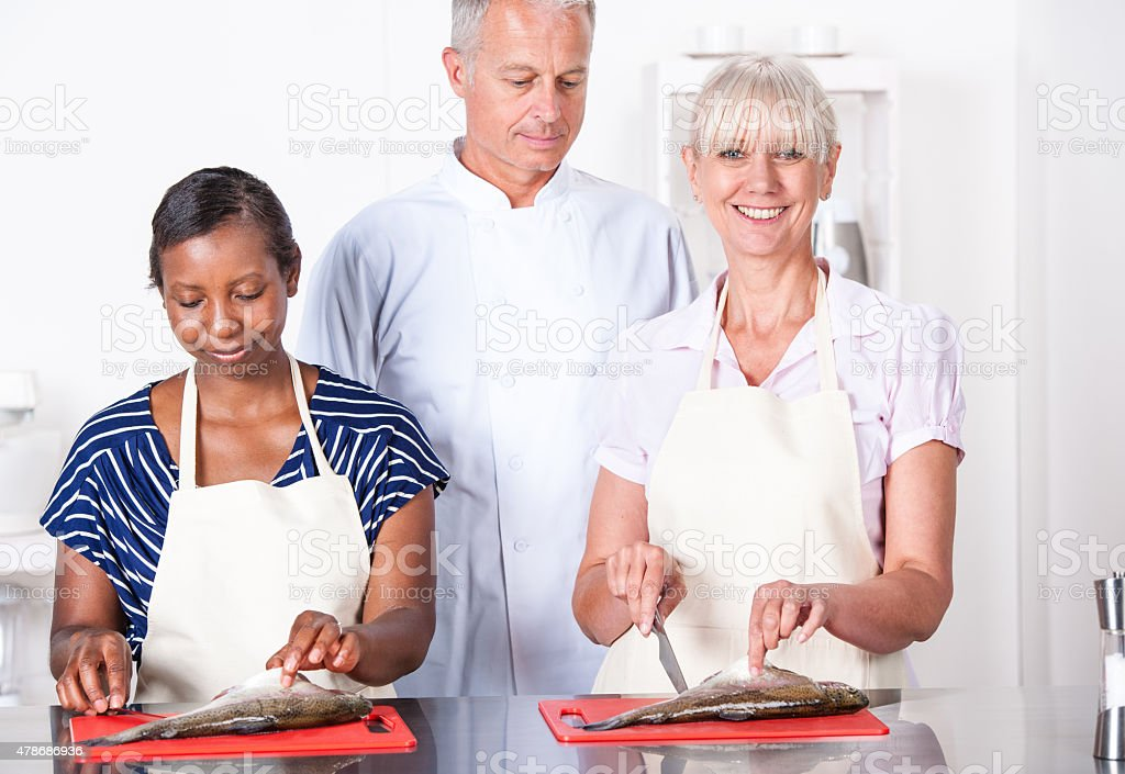Chef Assisting Appentices/ Students Preparing Fish In A Commercial Kitchen stock photo