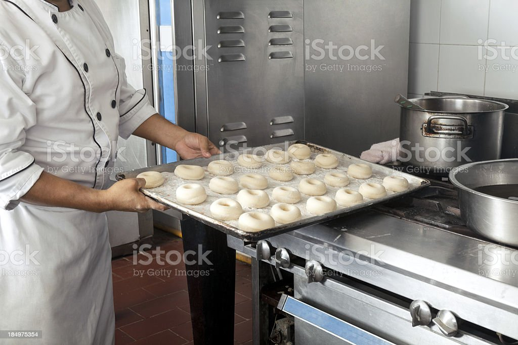 Chef baking doughnuts in a commercial kitchen royalty-free stock photo