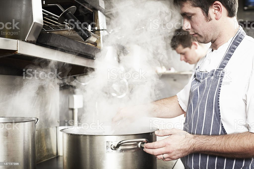 Chef boiling water in kitchen stock photo