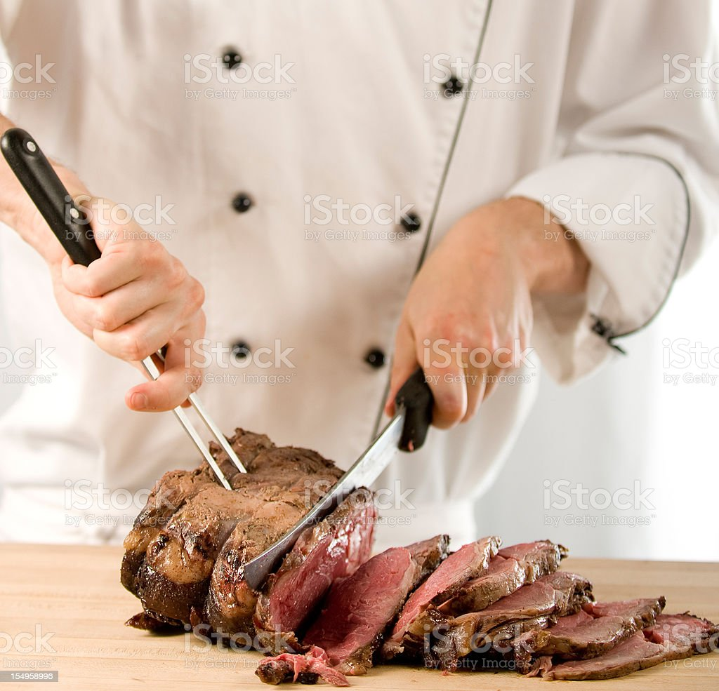 Chef carving perfectly cooked prime rib roast beef stock photo