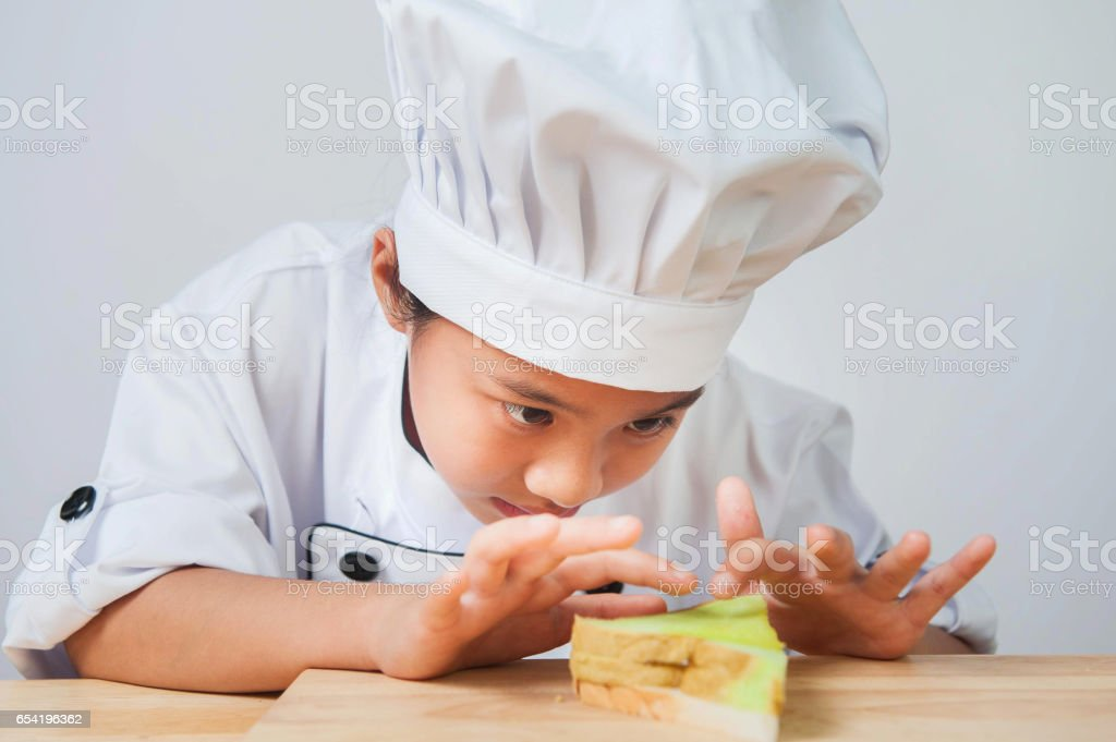 chef child,Girls wear chef costumes She is cooking intently stock photo