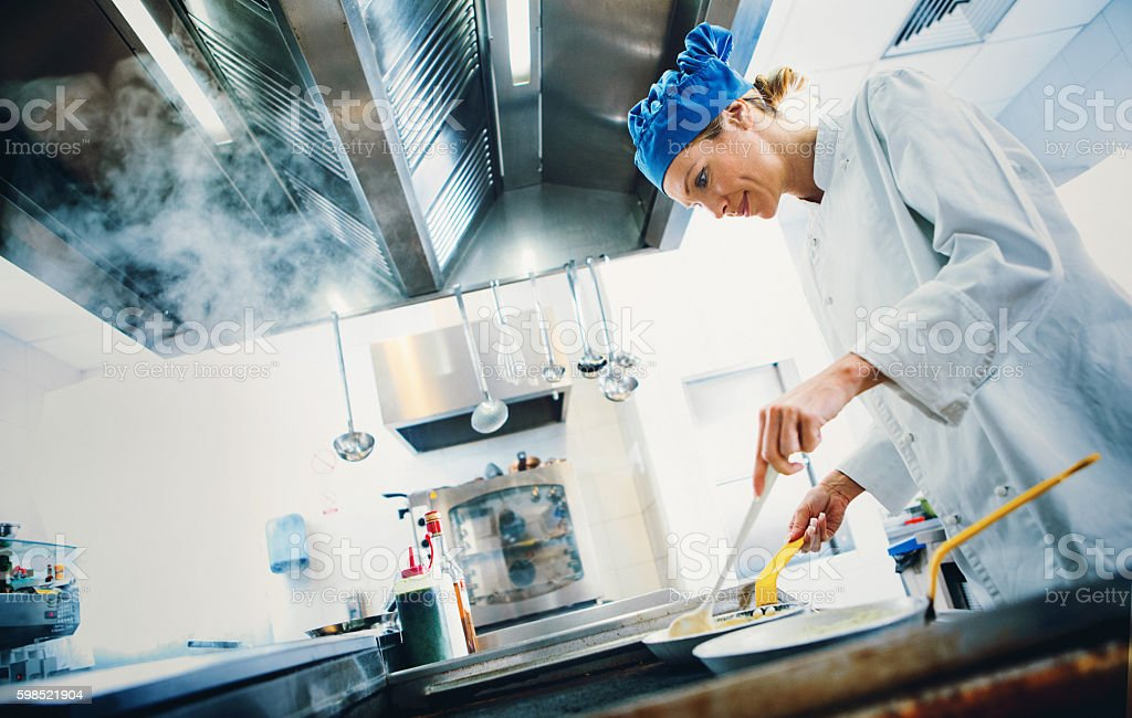 Chef cooking at a restaurant kitchen. stock photo