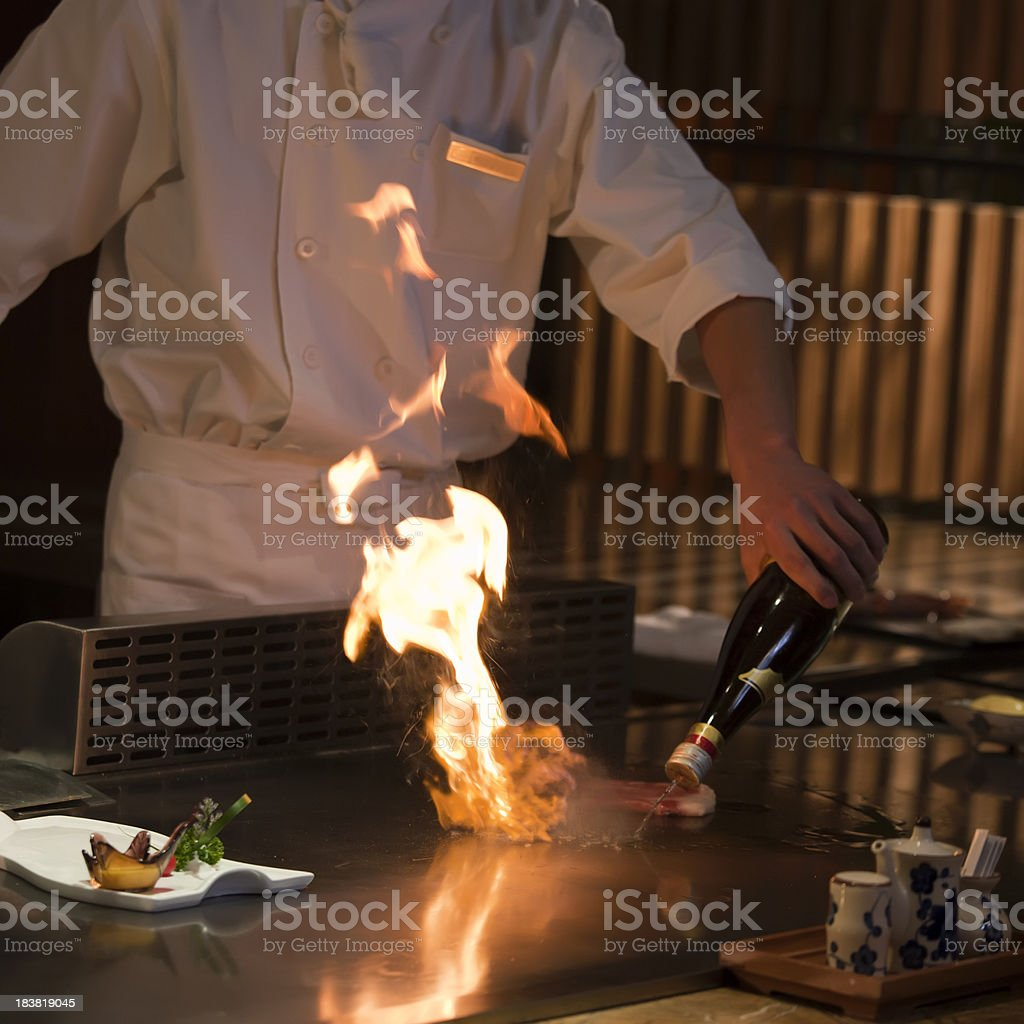 Chef cooking food on an iron griddle, teppanyaki-style stock photo