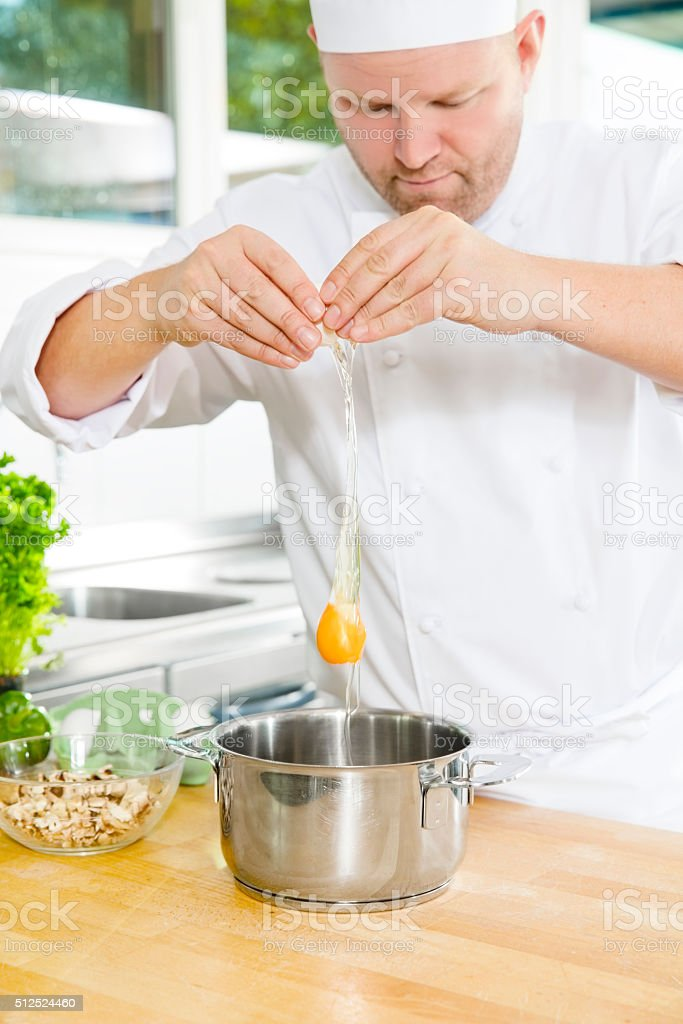 Chef cracking egg in large kitchen stock photo
