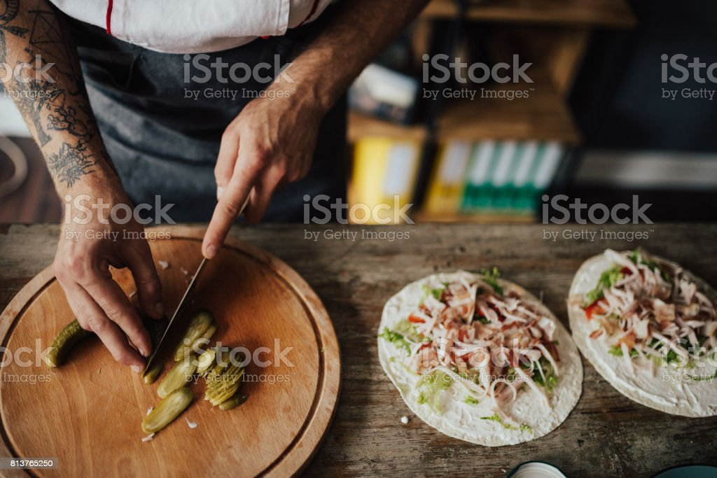 Chef cuts picles in thin slices for wrap sandwich stock photo