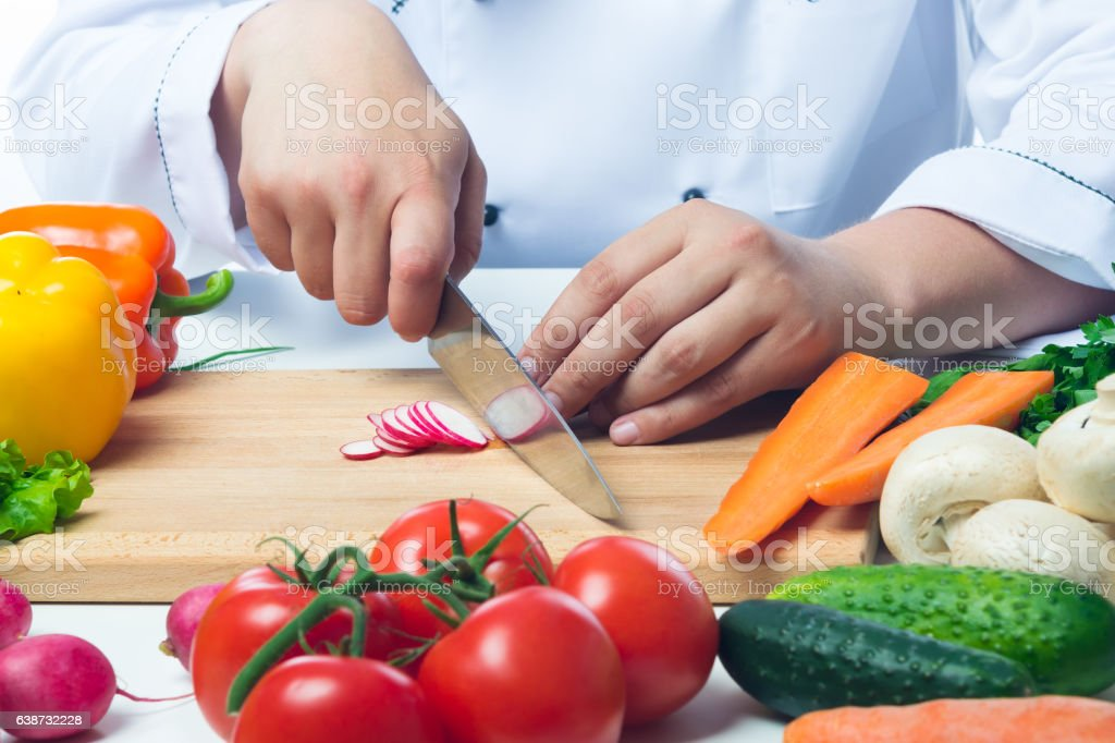 Chef cuts radishes in a vegetable salad stock photo