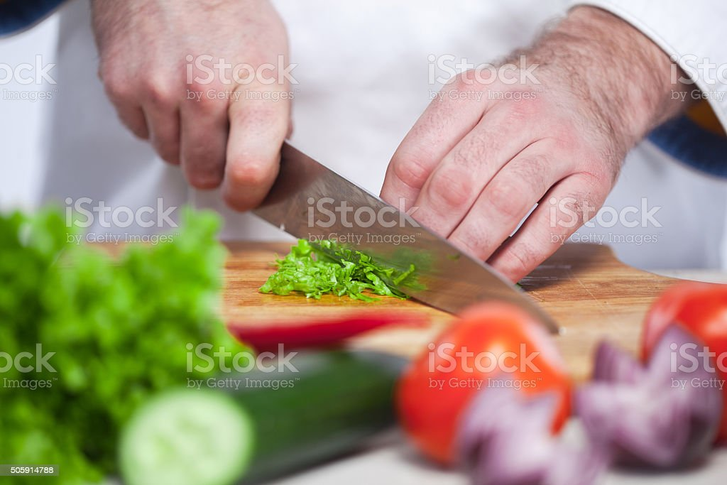 Chef cutting a green lettuce his kitchen stock photo