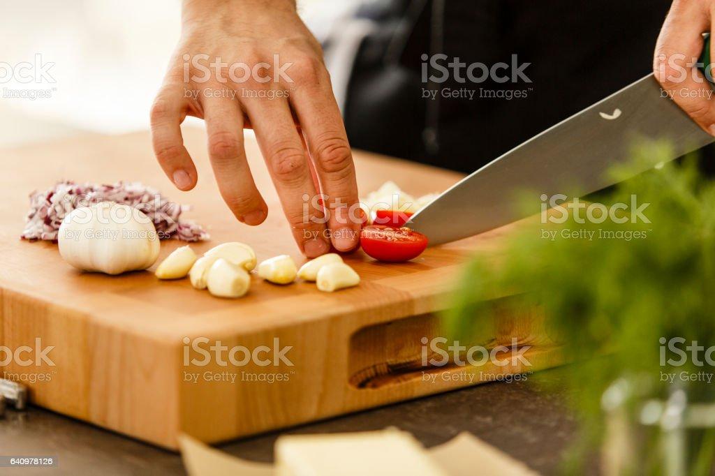 Chef cutting cherry tomato on cutting board stock photo