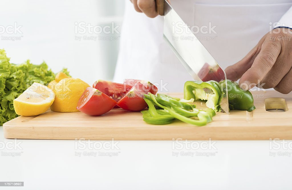 Chef cutting fresh vegetables on cutting board royalty-free stock photo