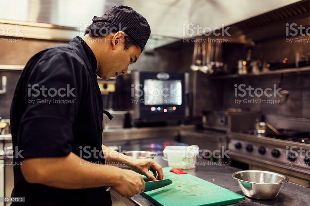 Chef Cutting Green Hot Paprika. stock photo