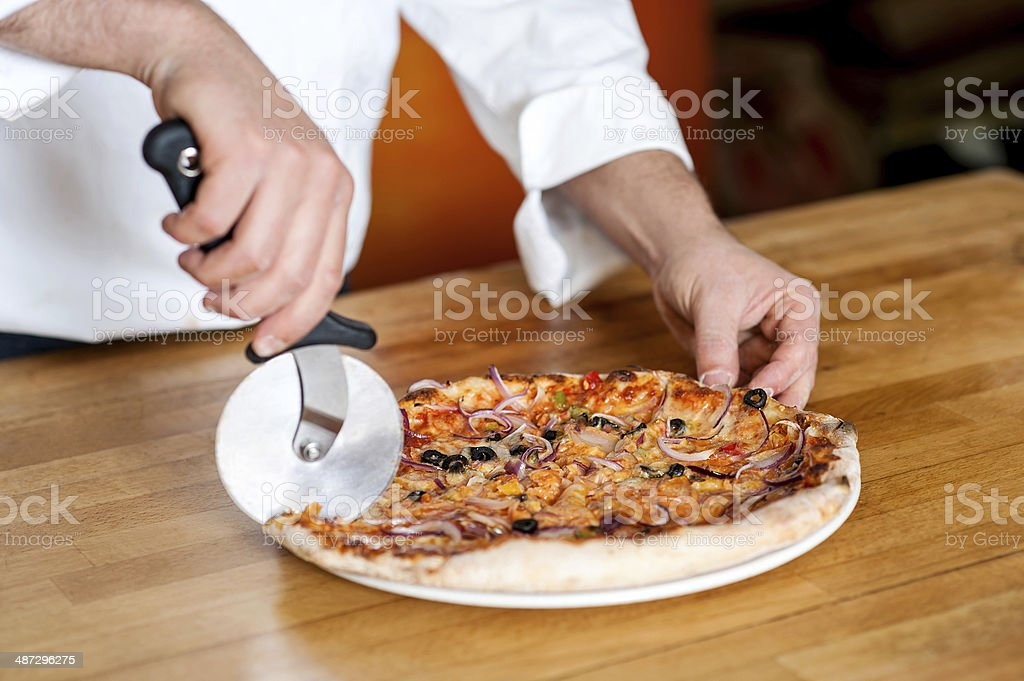 Chef cutting pizza with cutter stock photo