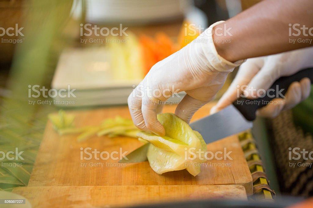 Chef cutting starfruit stock photo