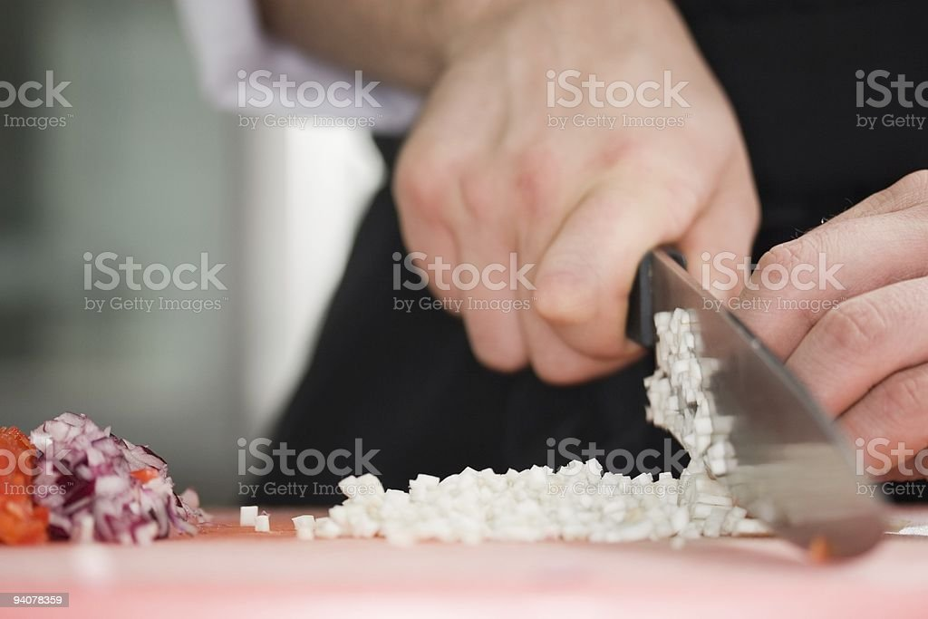 Chef cutting the onions on a wooden board stock photo
