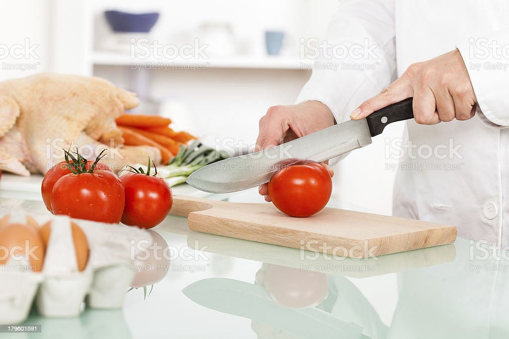 Chef cutting tomatos in the kitchen royalty-free stock photo