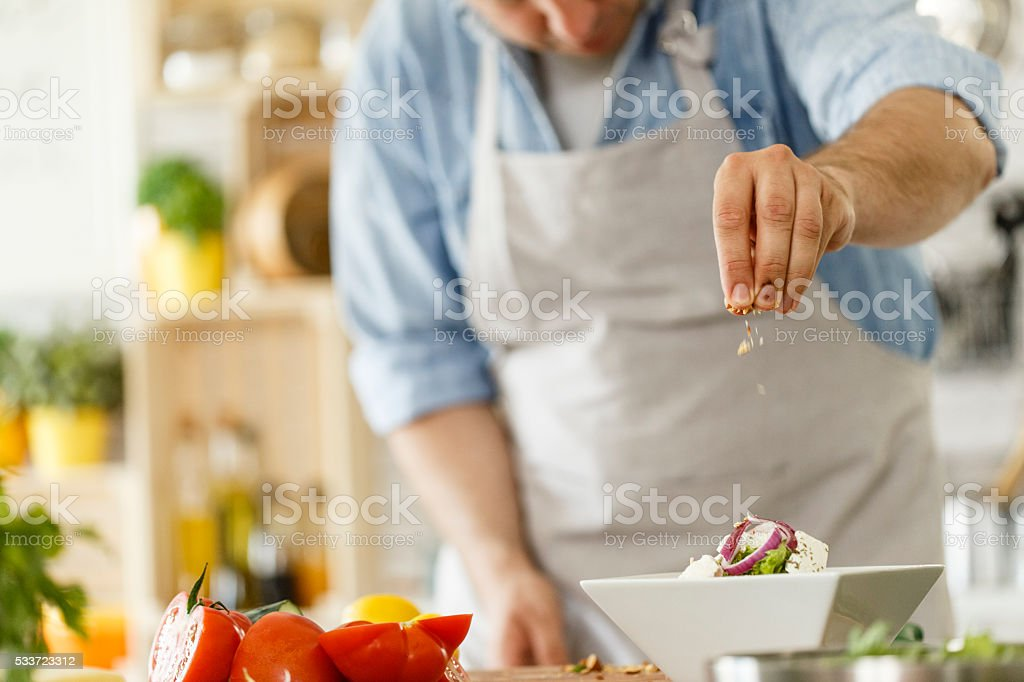 Chef decorating a plate with healthy salad stock photo