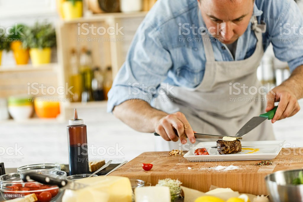 Chef decorating grilled beef stock photo
