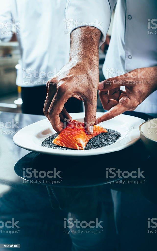 Chef dips salmon fillet on poppy seeds stock photo
