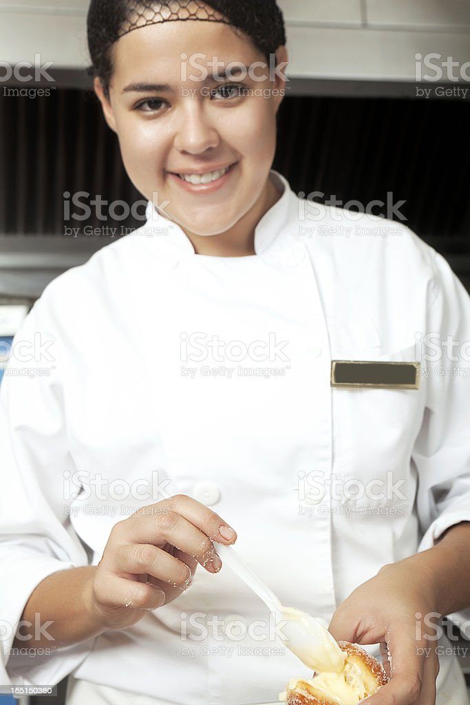 Chef filling a pastry cream puff royalty-free stock photo