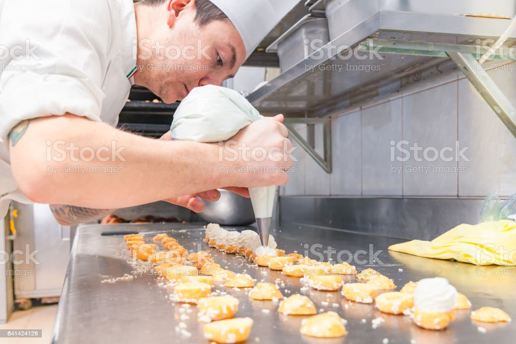 Chef filling small sweet pastries stock photo