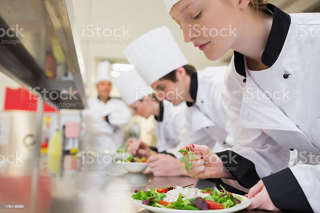 Chef finishing her salad in culinary class stock photo