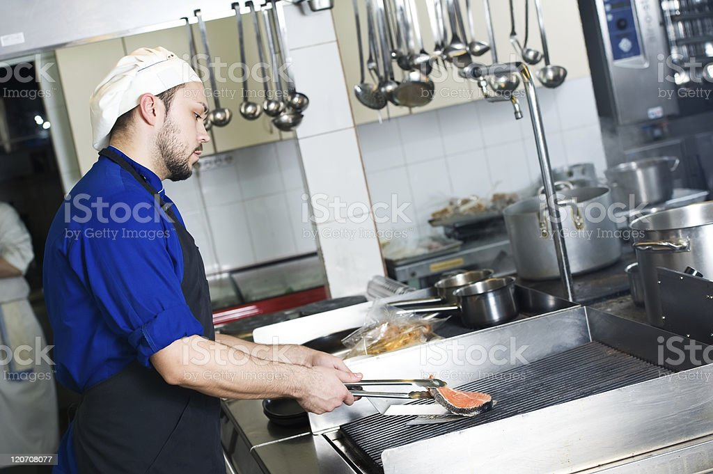 chef frying a fish on grill royalty-free stock photo