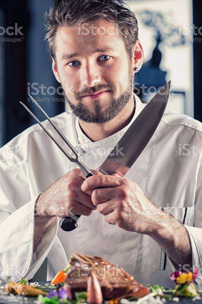 Chef funny. Professional Chef with knife and fork arms crossed. stock photo