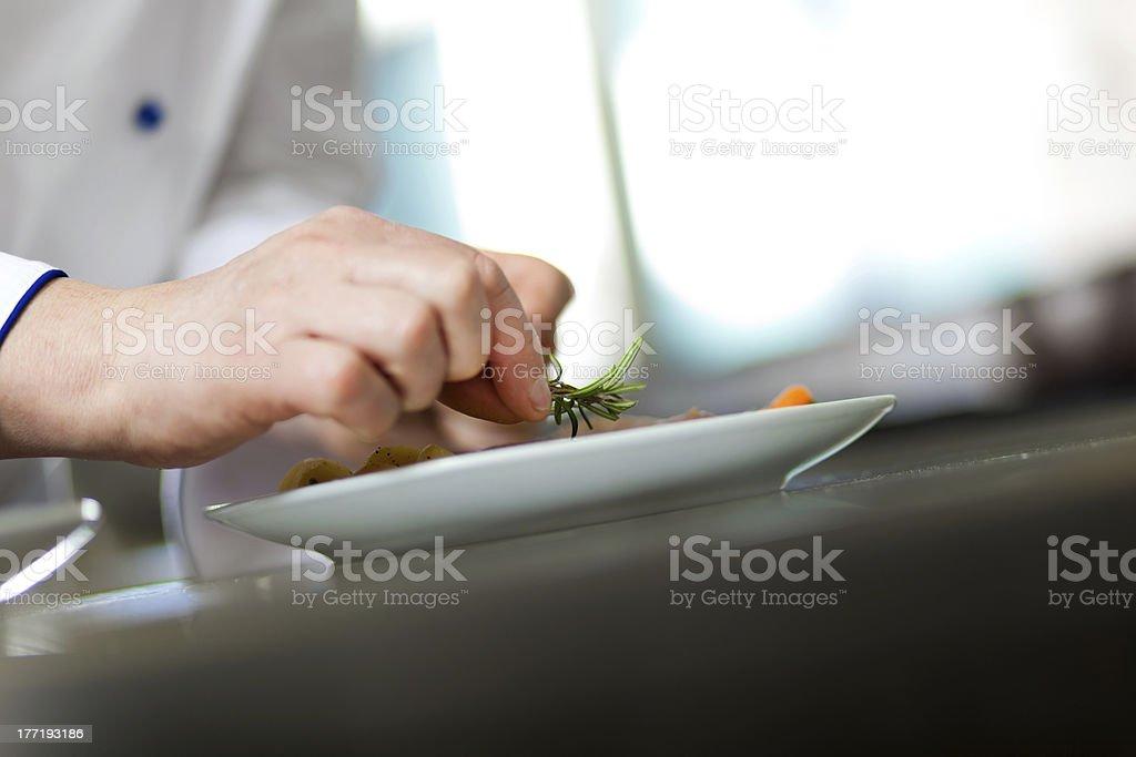 Chef garnishing a dish royalty-free stock photo