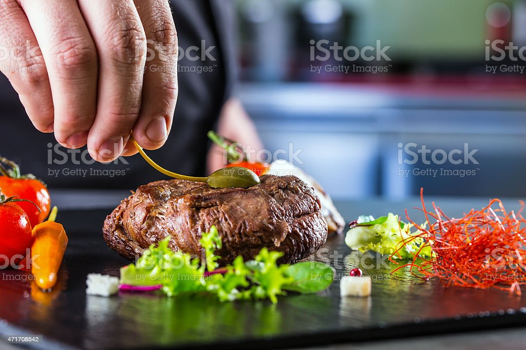 Chef garnishing a thick steak before it's served stock photo