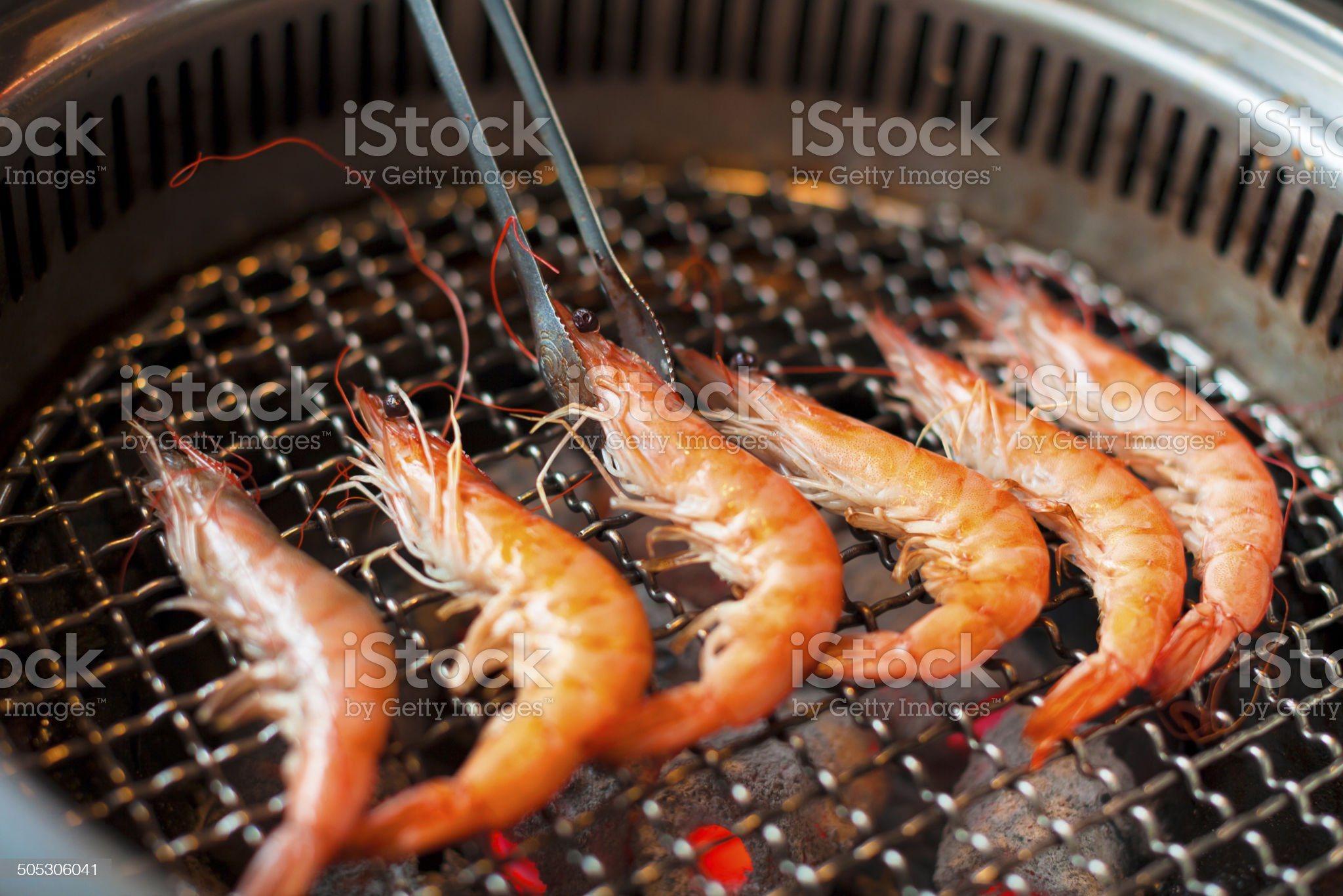 chef grilling shrimps on flame with tongs royalty-free stock photo
