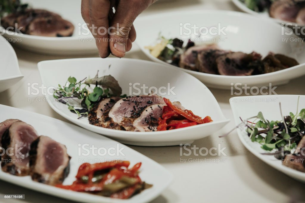 Chef hand adding black salt to a meat dish. stock photo